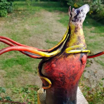 Hästskulptur med böljande man och svans som skiftar från svart över rött och gult