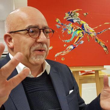 Foto på konstnären Melker Garay framför en av hans färgsprakande tavlor
