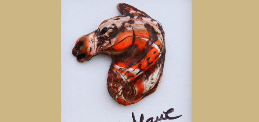 Litet porträtt i polymelera av hästhuvud i jordnära röda färger