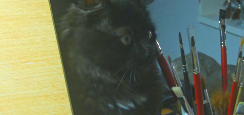 En svart kattunge som tittar på en burk med akvarellpenslar