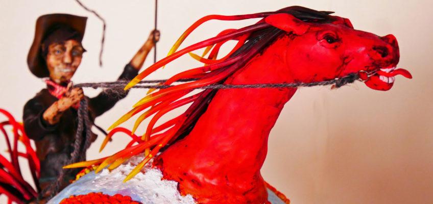 En röd häst som är en jordglob piskas framåt av en cowboy