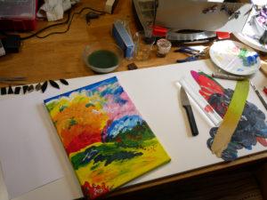 Ateljébord med påbörjad tavla i klara färger.