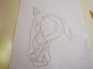 Stiliserat hästhuvud ritat med blyerts.