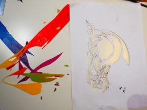 Papper med utskurna former och veneerbitar i klara färger.