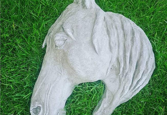 Hästhuvud i betong på gräsmatta