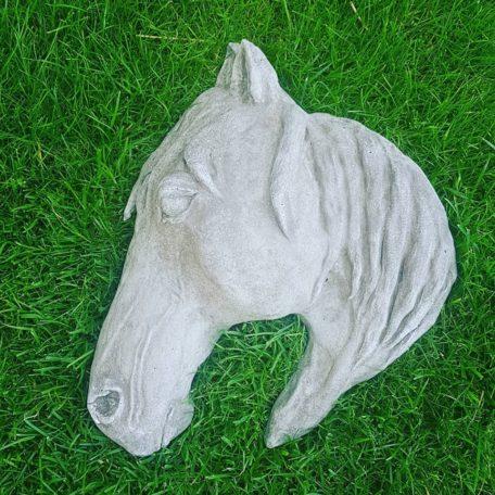 Hästhuvud i betong som ligger på en gräsmatta