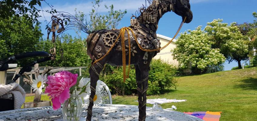 Hästskulptur med nycklar och hänglås som står på ett bord i solskenet