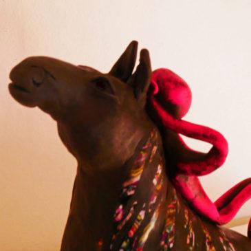 Skulptur med liten figur som vilar på en hästrygg