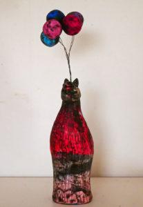 Liten stiliseradhäst i polymerlera med fem ballonger svävande över huvudet