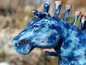 Huvudet på en blå hästskulptur som ser ut som ett coronavirus