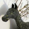 Huvud på en hästskulptur med kvistar som man