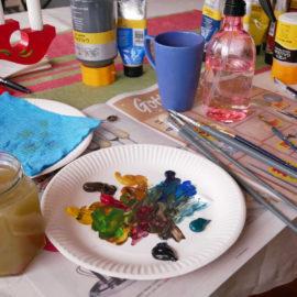Målarmaterial, akrylfärger och penslar på ett bord