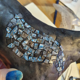 Small pieces of cured clay on the body of a polymer clay horse sculpture