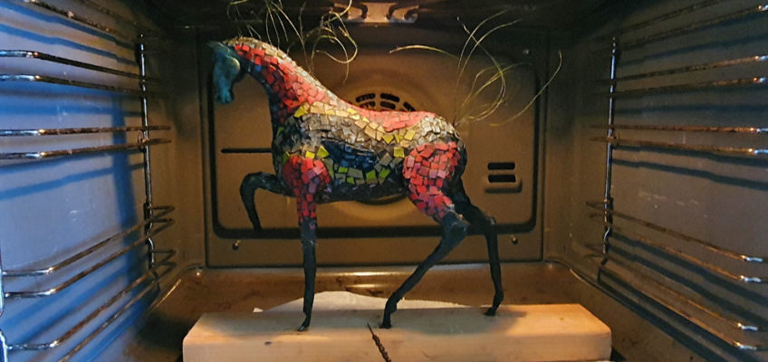 A polymer clay horse sculpture is cured in the oven