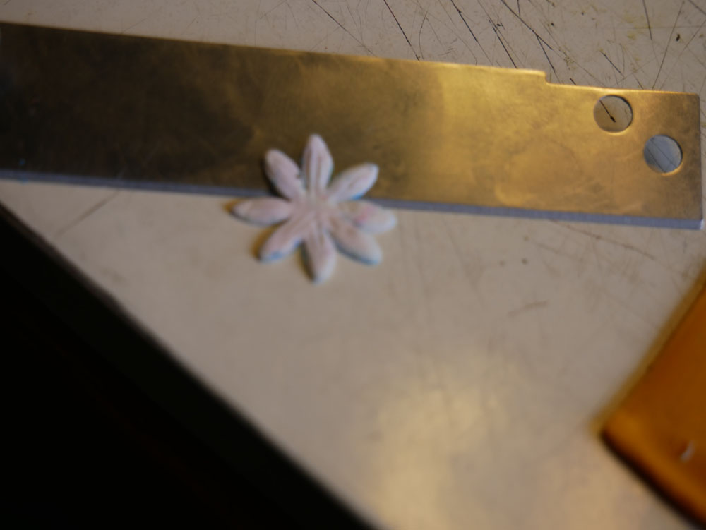 a white polymer clay flower and a cutting blade