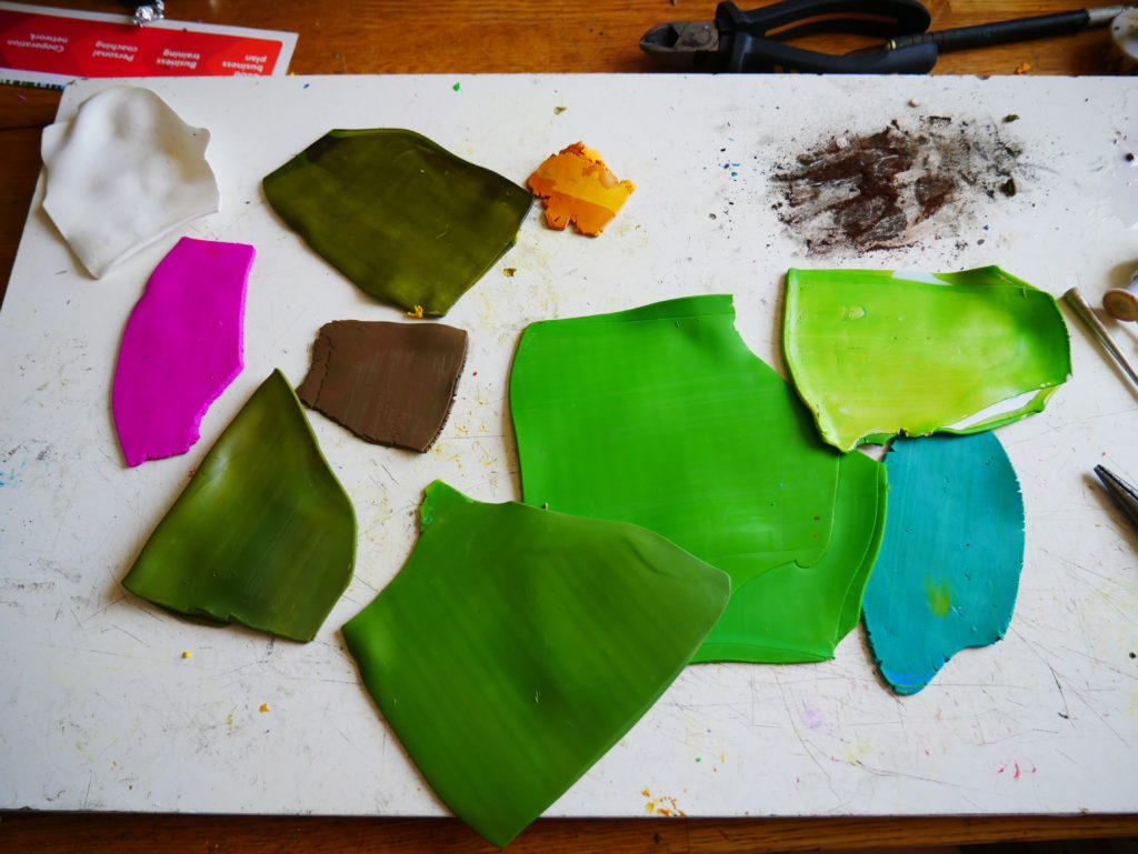 Sheets of polymer clay in mostly green hues.