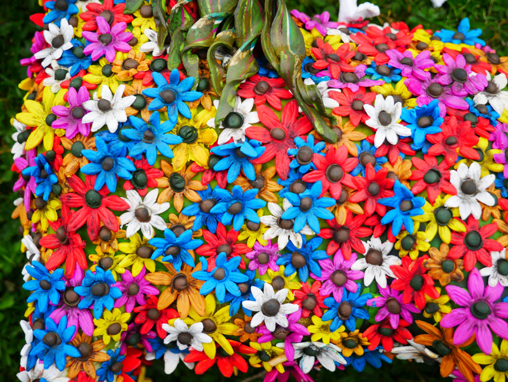 Horse sculpture covered on flowers, with a man standing on its back